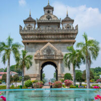 Picture of the Patuxai monument in downtown Vientiane, Laos. The sky is beautiful and blue and the monument looks like a French Arch with a distinct southeast Asian influence. There is a beautiful fountain, flower beds, and palms, in front of it.
