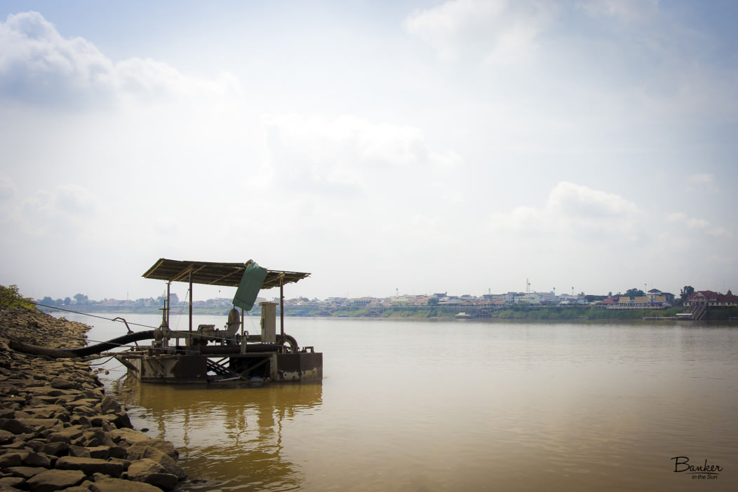 Picture of a lone water pump by the bank of the Laos side of the ...