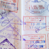 A US passport with many Chiang Mai to Laos visa run stamps from Thailand.