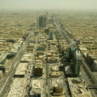 A very dusty skyline of the city of Riyadh in Saudi Arabia. The buildings are yellowed and old and the place looks a little disorganized and busy. The landscape beyond is very flat.