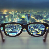 Picture of glasses looking out onto a new city skyline at night. It is focused through the lenses of the glasses, which are resting on a ledge, and which signify getting a fresh start abroad.
