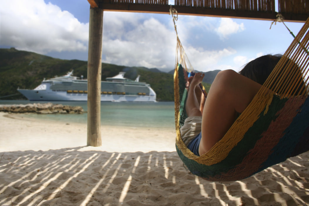 Man relaxing in a hammock on a beautiful beach. A large cruise ship can be seen in the distant lagoon.