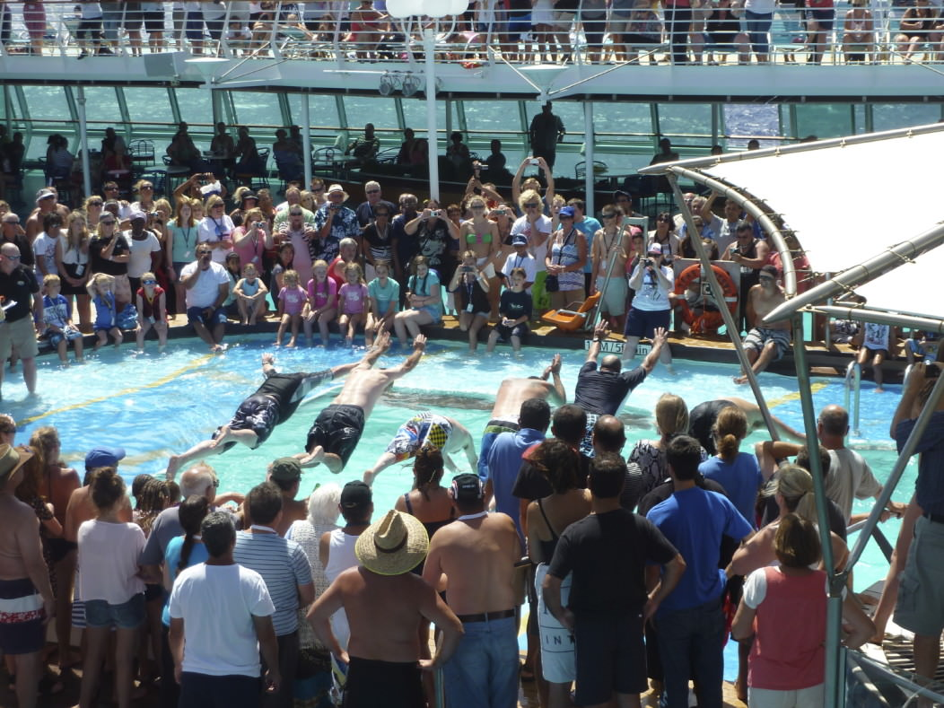 Picture of passengers on a cruise ship jumping in a pool. A large crowd of beautiful people stand around the pool, cheering.