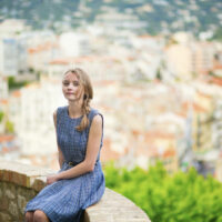 Cannes, France and the French Riviera: beautiful woman city on the railing of a villa overlooking Cannes.