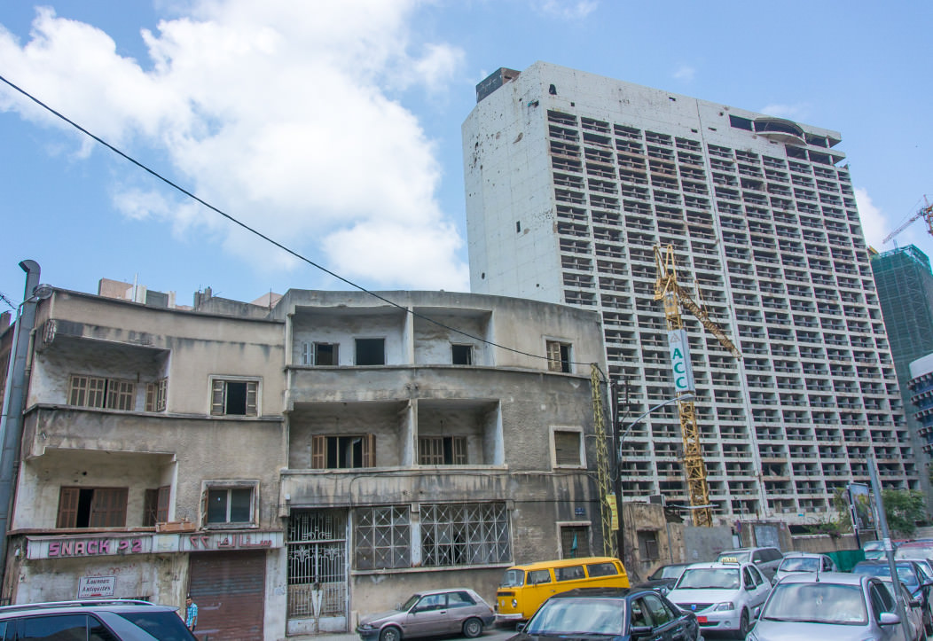 a picture of the bombed-out buildings and hotels in downtown Beirut, Lebanon. The facades are riddles with bullet holes and rocket fire.