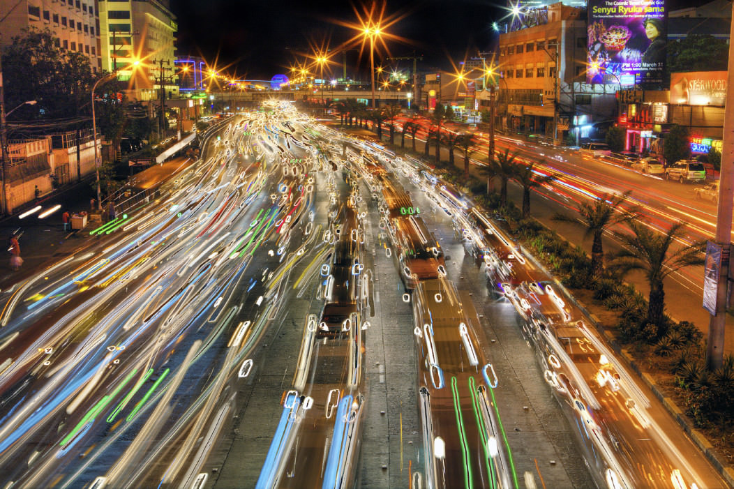 The EDSA Highway in downtown Manila in the Philippines. The picture is at night and the traffic lights are blurred as they speed by. The streets are colorful and full of neon and multi-colored lights.