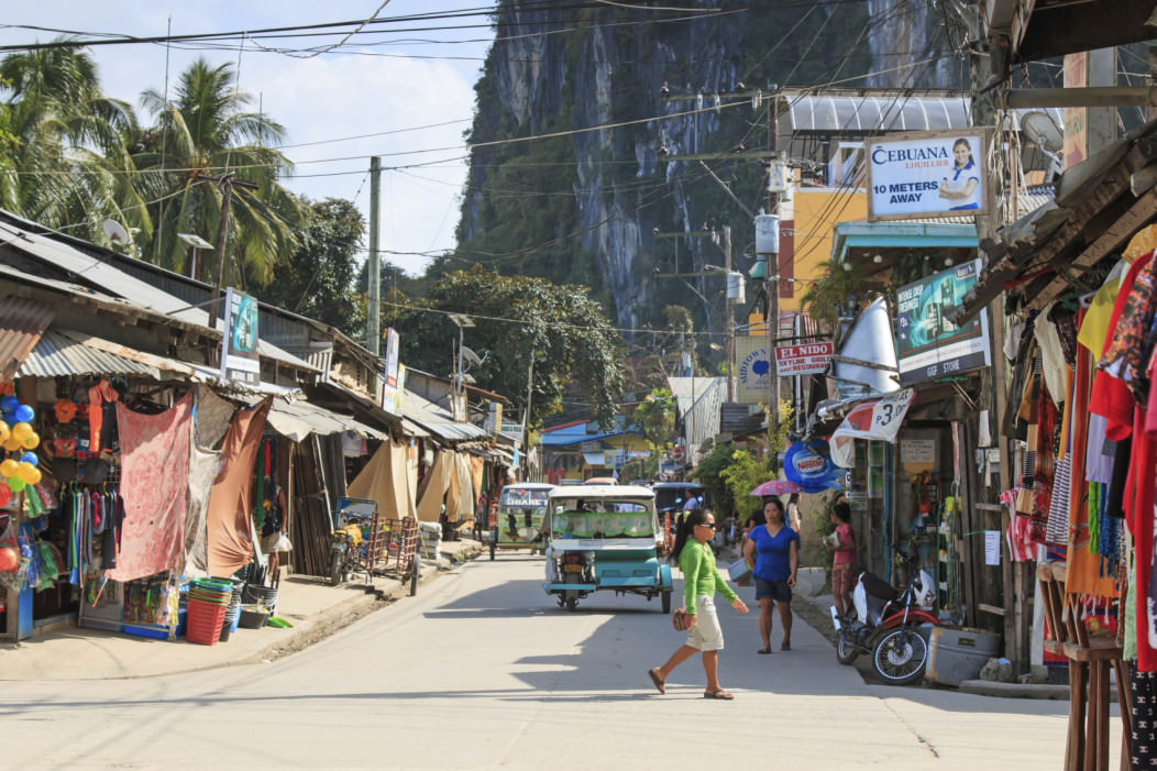 A busy street in El Nido, Palawan in the Philippines. Street stalls line the sides of the street and a beautiful limestone cliff looms in the background.
