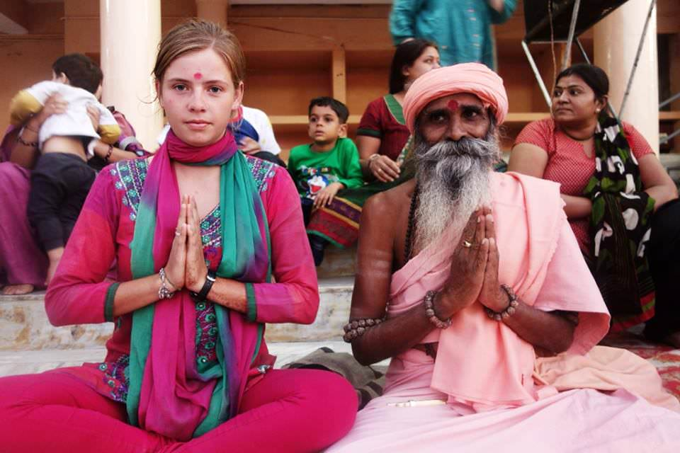 A photo of the beautiful name, Shirine Taylor, who is sitting cross-legged next to a Shaman in India. She is meditating and wearing a pink traditional Indian outfit, with a red dot on her forehead.