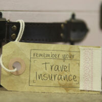 Travel insurance tag on the handle of an old suitcase.