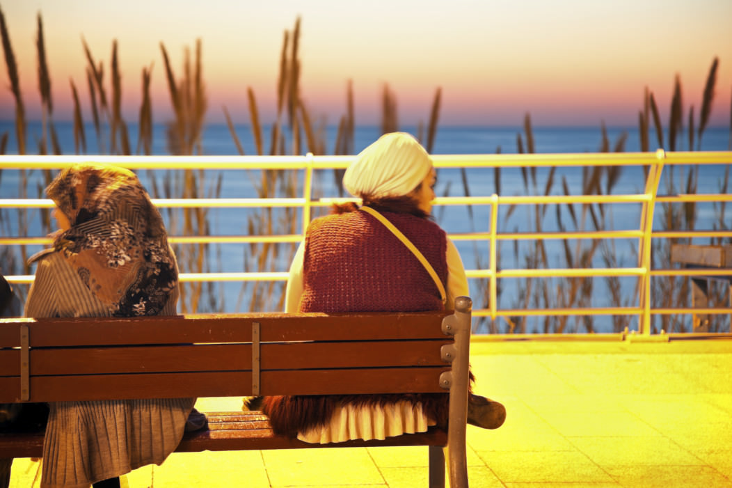 Women sitting in front of a beautiful sea at sunset in Beirut's Corniche, Lebanon