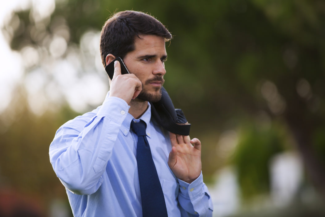 A Western banker making a followup call on his cell phone. He is wearing office attire, a shirt and tie, and has a jacket slung over one shoulder. He is outdoors.