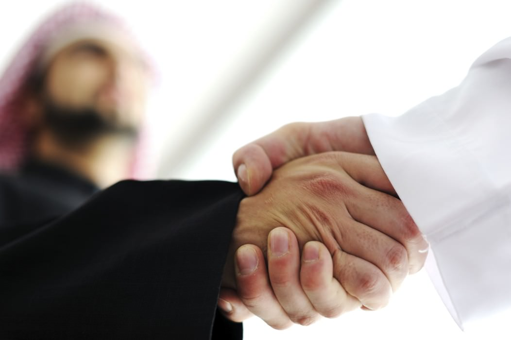 Closeup of two businessmen shaking hands in the UAE. One of them looks defocused and wears a traditional head-dress known as the shmagh.
