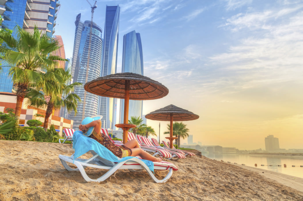 Tourists relaxing on the beautiful beach of Abu Dhabi, UAE. Tall, very modern skyscrapers rise up in background of the beach.