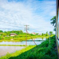 Cheap train ride from Bangkok to Chiang Mai. The Thailand scenery and landscape outside the train looks beautiful and green. A few rice fields and houses can be seen.