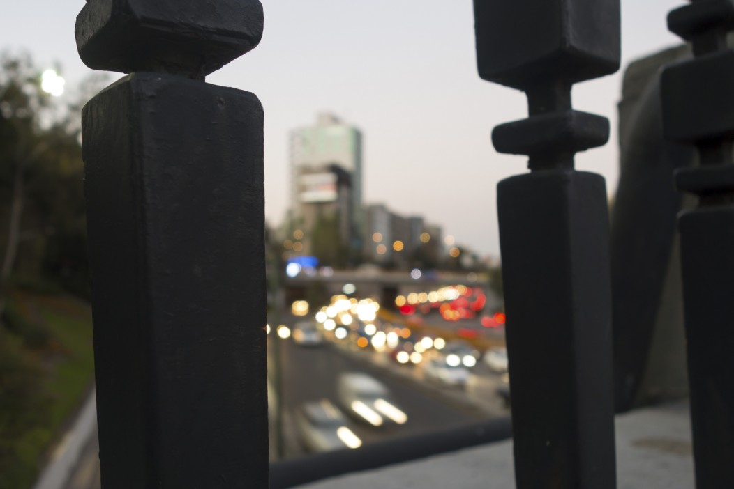 A defocused photo of the highway and traffic in Mexico City, Mexico. It is taken from behind bridge railings.