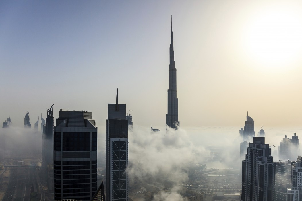 A panoramic foggy skyline of Dubai in the UAE. Plenty of skyscrapers rise out of the fog, many of them bank buildings. The Burj Khalifa can also be seen rising up from the carpet of fog.