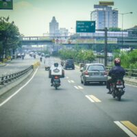 Main Highway in downtown Jakarta, Indonesia. There are care and motorcycles, and a vintage, old look to the picture.