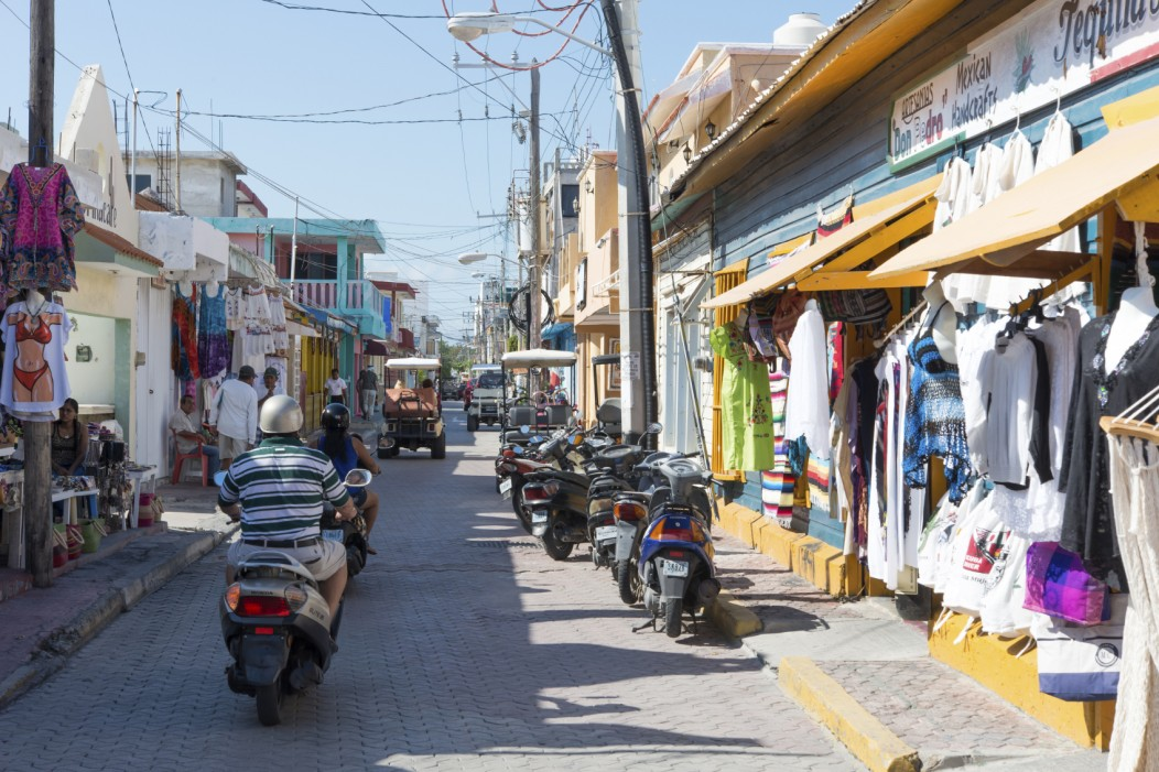 The colorful streets and shops of Isla Mujeres, Mexico. The street is calm and souvenir shops line the sidewalk.