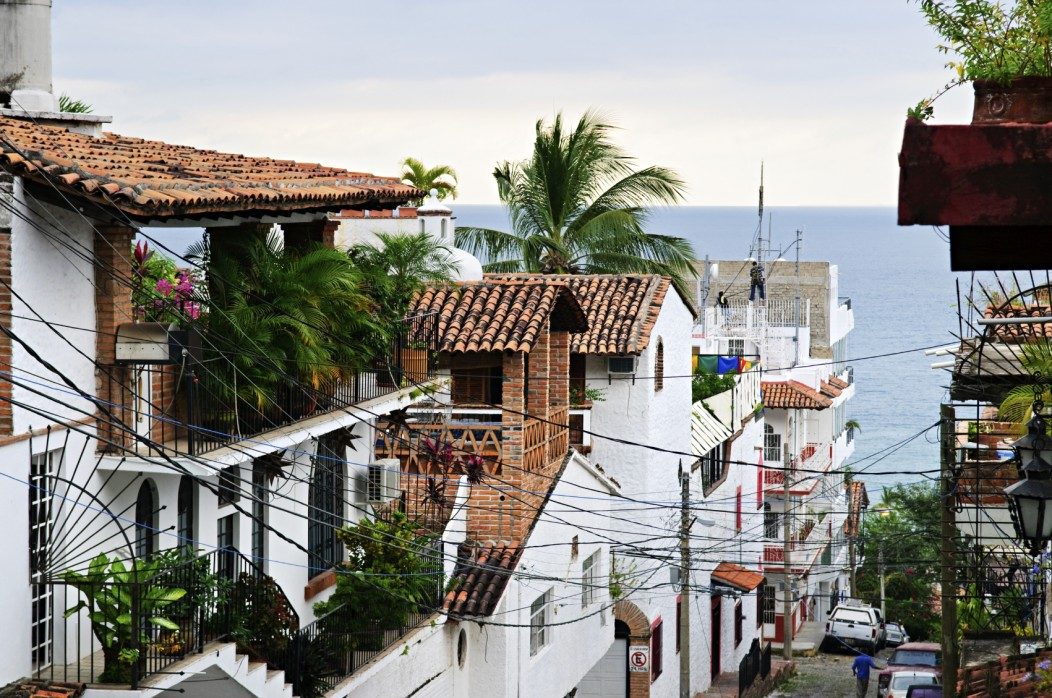 Beautiful street and houses of Puerto Vallarta, Mexico. The ocean can be seen in the background, and the white houses in the foreground.