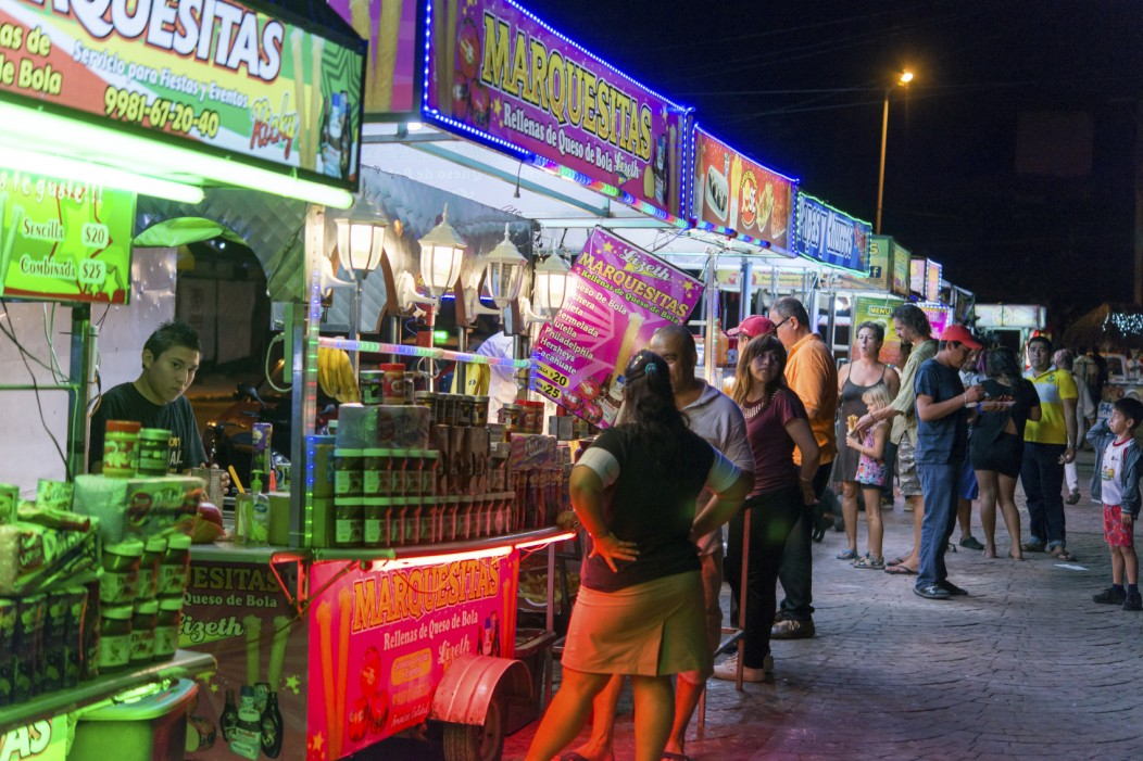 Colorful Mexican street food vendors selling food to tourists in Cancun, Mexico.