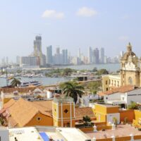 The beautiful skyline of the colonial city of Cartagena in Colombia. The modern buildings can be seen in the distance, and colorful colonial houses in the forefront.