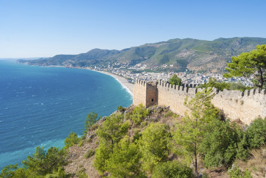 The beautiful coastline and castle of Alanya, Turkey. The mountains are in the background, along with the beautiful beach and light blue water. Trees and the castle walls are in the foreground.