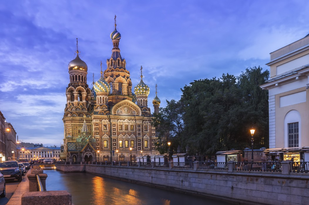 An evening picture of the Church of the Saviour on Spilled Blood in Saint Petersburg, Russia. The beautiful gold and colored domes are lit up at night.