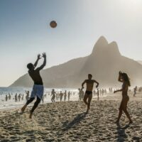 Beautiful Brazilian women and men playing volleyball on Ipanema Beach in Brazil.