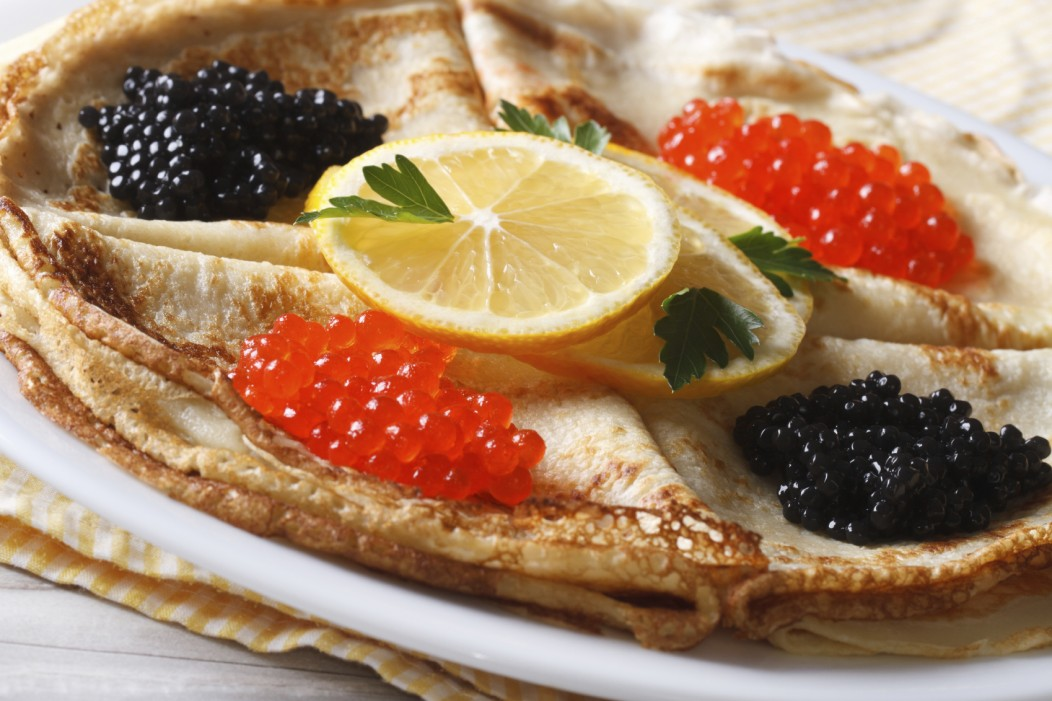 Traditional Russian dish: red and black caviar crepes topped with lemon and herbs.
