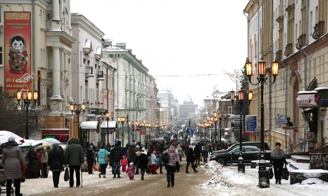 Snowy winter streets in Novgorod, Russia. Many shops line the street, which looks romantic and wintered.