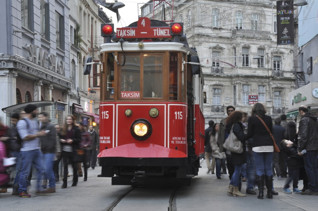 The crowded Taksim Istiklal Street and its red tram in Istanbul, Turkey. Plenty of tourists are walking around and the architecture looks almost European.