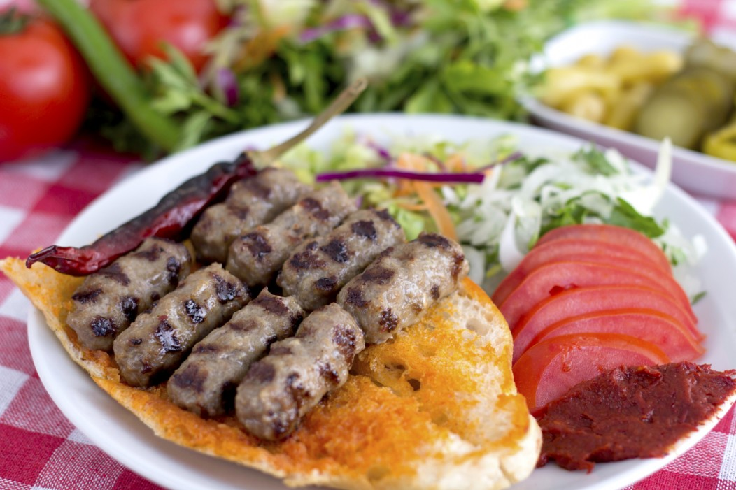 A traditional Turkish dish of lamb kebab laid on pita bread and served with a side of mixed vegetables.