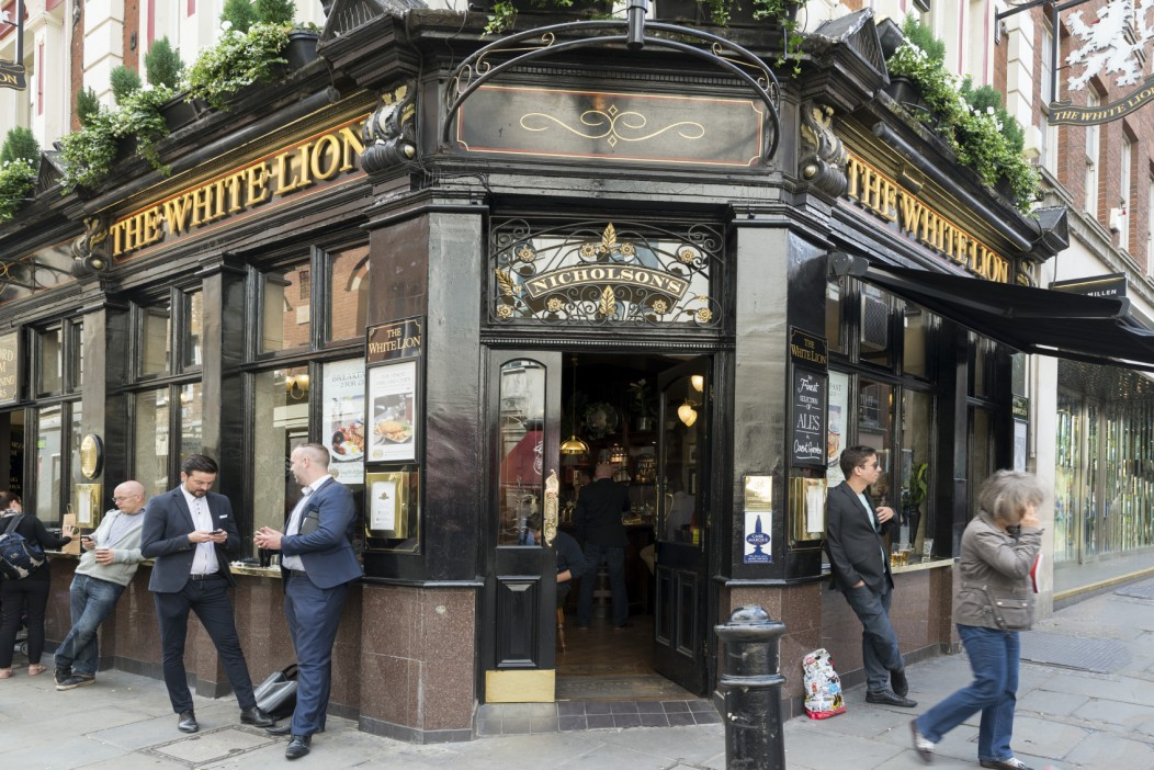 "A typical street side pub in London, UK. Several people stand outside, talking. The pub is called ""The White Lion""."