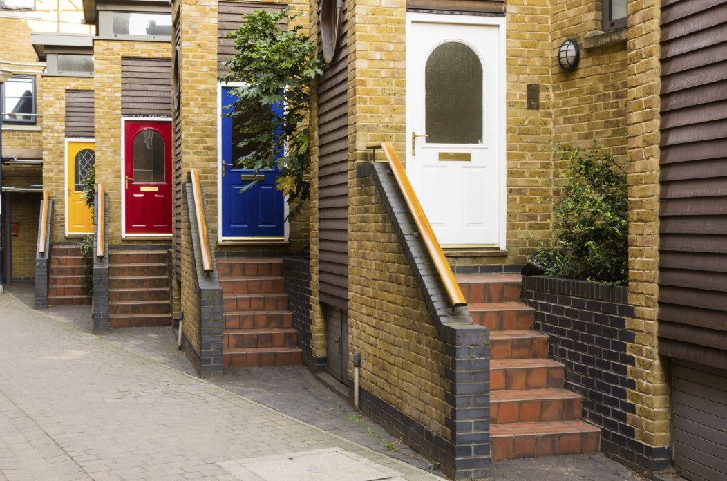 Accommodations in the UK: Colored doors and stairs leading to townhouses in a suburb of London.