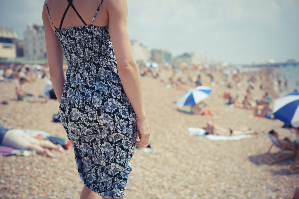 Beautiful young woman wearing a short dress at a beach in the UK. The photo is defocused and the girl, her back to us, is in focus. The beach looks crowded.
