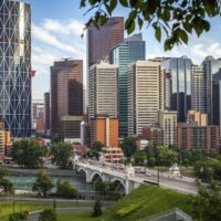 A pretty skyline of the city of Calgary, Canada. The city looks very modern and surrounded by parks.
