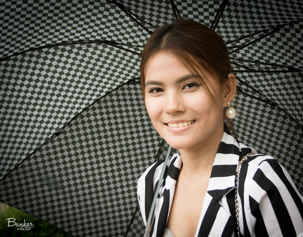 A beautiful Thai woman wearing elegant clothes and holding an umbrella.
