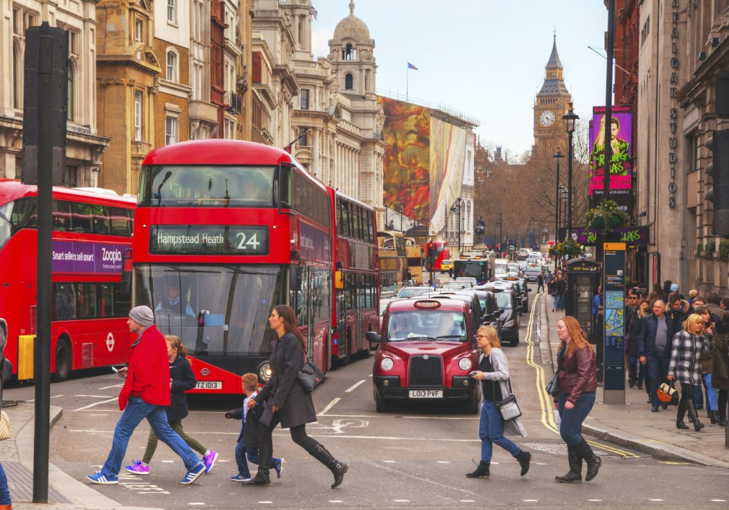 Street of London with many red buses and taxis at stop. The backdrop is of the beautiful Victorian buildings on this narrow street.