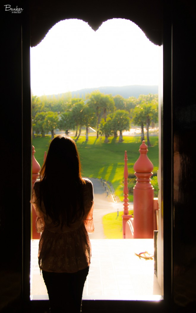 Silhouette of a Thai girl in a temple with a lush forest background that is faded and soft.