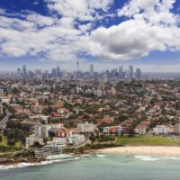 Panoramic skyline of Sydney city and its beach in Australia. Partially cloudy but sunny day.