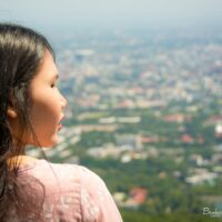 Profile of a pretty Thai woman in front of a defocused panorama of Chiang Mai, Thailand.