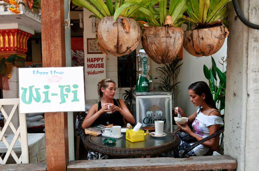 "A couple of digital nomads sitting a cafe in South America. The outdoor cafe looks tropical and has a ""wifi"" signboard nailed to a post."