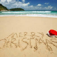 "A Thai beach with a Santa hat on the beach and ""Merry Christmas"" scribbled in the sand."
