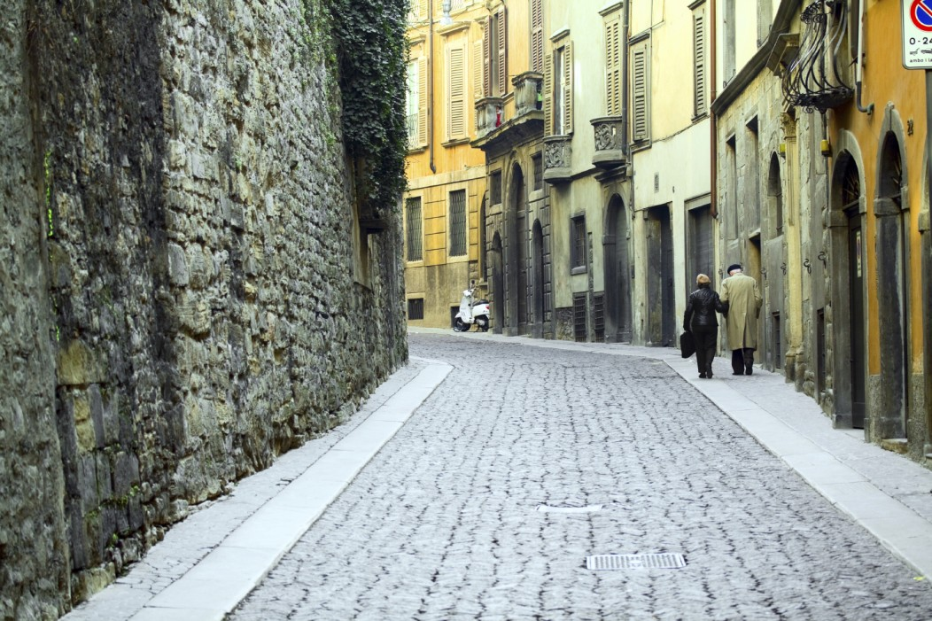 Cobblestone narrow street of Bergamo, Italy with an old couple walking the old buildings.