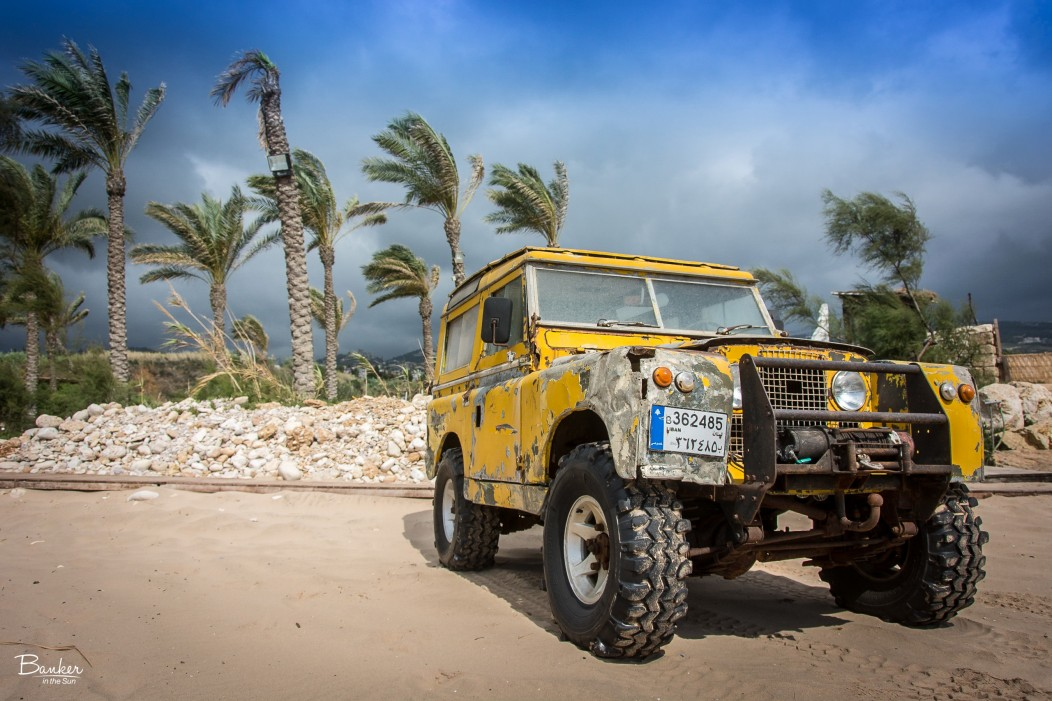 An old jeep truck on a stormy beach with palms swaying in the winds in the background.