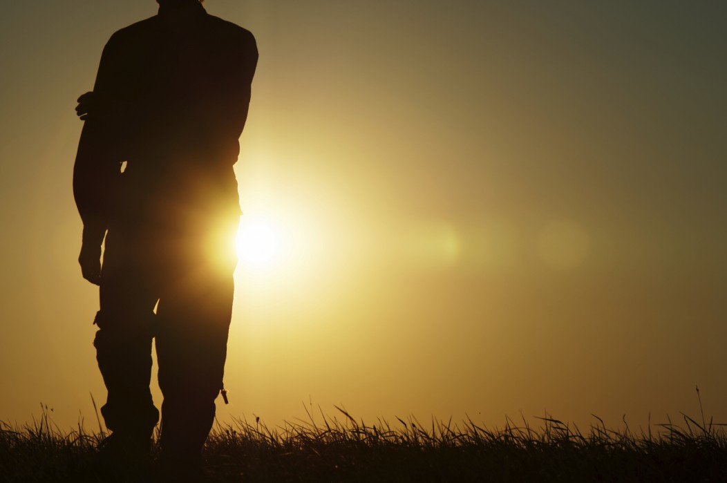The silhouette of a free-spirited backpacker on a field during a sunset.