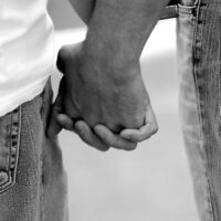 Closeup of the hands of two gay men holding hands. Black and white photograph with a defocused sea in the background.
