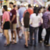 A defocused photo of Thai people walking in the very busy streets of Bangkok in Thailand.