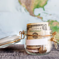 Picture of a jar with rolled dollars inside and a world map in the background.