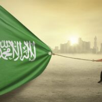 Picture of a sunset over a Saudi Arabian city with a man in the foreground pulling a Saudi flag across the photo.